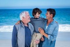 Membres de la famille masculins posant à la plage images stock