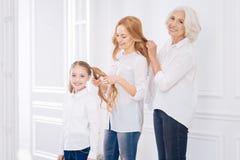 Membres de la famille positifs faisant des coiffures l'un pour l'autre Photographie stock libre de droits