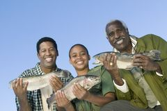 Membres mâles de famille affichant des poissons Image stock