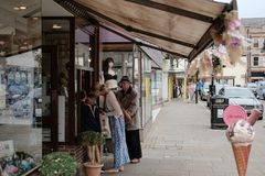 Membri dei gelati d'acquisto veduti pubblici ad un contatore in una via principale inglese fotografia stock
