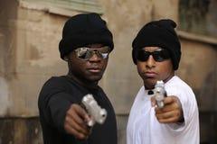 Membri del gruppo con le pistole sulla via Immagini Stock