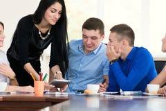Membri del team che ascoltano attentamente una donna di affari castana Immagine Stock