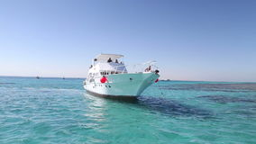 Membri della squadra che ancorano la barca accanto al mare dell'isola di paradiso in rosso stock footage