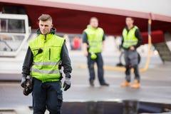 Membro de pessoal de terra seguro que está na pista de decolagem do aeroporto foto de stock royalty free