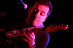 Membro del gruppo che gioca assolo della chitarra sulla fase, primo piano Fotografia Stock