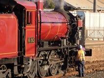 Membro do grupo de trem que inspeciona e que lubrifica sua locomotiva na estação de Bendigo fotos de stock royalty free