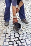 Membro do grupo que derrama o passo derretido de uma cubeta do alcatrão Foto de Stock