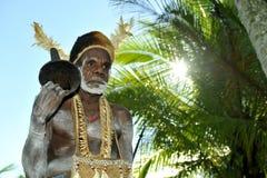 Membro duma tribo de Asmat com cilindro Na vila de Asmates vai a preparação para de uma cerimônia de Doroe Imagens de Stock