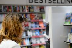 Membro là di pubblico visto esaminare i libri come si vede in un giornalaio ed in una libreria della via principale immagine stock