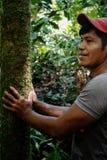Membro tribal do ticuna local que procura um log para cair no meio da floresta úmida foto de stock
