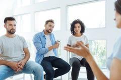 Membros agradáveis sérios do grupo da terapia que escutam seu amigo Imagens de Stock