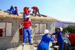 Membros da Comunidade diversos que constroem uma casa do baixo custo em Soweto fotos de stock royalty free