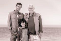 Membros da família masculinos que levantam na praia foto de stock royalty free