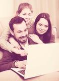 Membros da família que apreciam registrando o hotel em linha no portátil junto imagens de stock royalty free