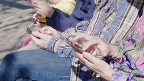 Membros da família que usam os telefones celulares exteriores, close-up das mãos video estoque