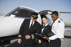 Membros do grupo da cabine que discutem relatórios junto Foto de Stock Royalty Free