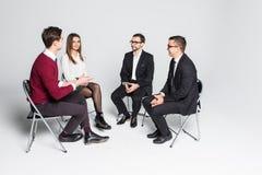 Membros do grupo de apoio que sentam-se nas cadeiras que têm a reunião isolados no fundo branco fotografia de stock royalty free