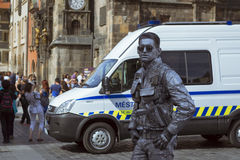 Meme-artist in the form of futuristic police posing on old Town Square Stock Image