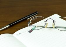 Memo. Pen and glasses on desk Stock Photo