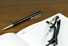 Memo. Pen and glasses on desk Royalty Free Stock Photography