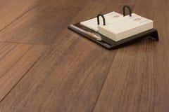 Memo Book on Laminated Flooring. Focus on the memo book stock photo