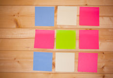 Memo note stick on wooden background. Multicolored memo note stick on wooden background royalty free stock images