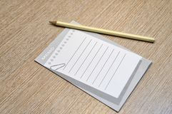 Pencil and memo pad concept. A memo pad and yellow pencil on wood office table. Copy space Royalty Free Stock Image