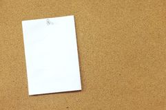 Memo pinned on cork noticeboard. Blank white memo paper pinned on brown cork office noticeboard Royalty Free Stock Photos