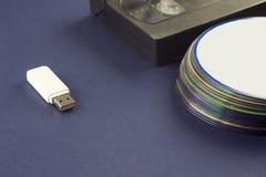 Memoria USB blanca en una cinta de video del fondo y un usb azules de los compact-disc foto de archivo