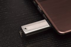 Memoria USB del metal del USB conectó a mano con un ordenador portátil fotos de archivo