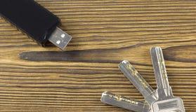 Memoria USB negra en un usb de madera del fondo y de las llaves imágenes de archivo libres de regalías