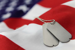 Memorial. Blank dog tags on American flag with focus on tags - Shallow dof Stock Image