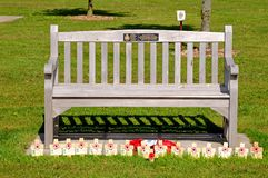 Memorial bench with poppies and crosses. Wooden bench with poppy memorials at the base at the National Memorial Arboretum, Alrewas, Staffordshire, England, UK Stock Images