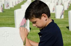 Memorial Day. A boy praying at a tombstone on Memorial Day at the National Cemetery in San Diego,CA Royalty Free Stock Photos