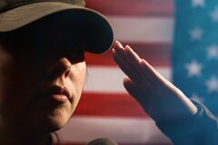 Free Memorial Day. A Female Soldier In Uniform Salutes Against The Background Of The American Flag. Close-up Portrait. Copy Space. The Stock Photos - 182178163