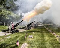 Memorial Day celebration in a veterans cemetery. Canons firing at a Memorial Day celebration in a veterans cemetery Royalty Free Stock Images