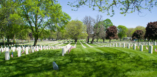 Memorial Day. A vast expanse of white grave markers at a Veteran's Cemetery, each adorned with US flags for Memorial Day Royalty Free Stock Image