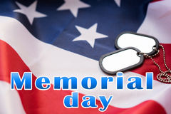 Memorial day words over american flag and dog tags Stock Photos