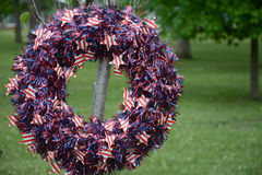 Memorial Day wreath. A Memorial Day wreath of red white and blue decorates a tree planted in the memory of a veteran royalty free stock photography