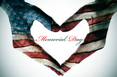 Memorial day. Written in the blank space of a heart sign made with the hands patterned with the colors and the stars of the United States flag