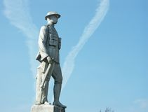 Memorial depicting world war 1 soldier. Stone sculpture to world war 1 dead depicting british soldier in uniform with rifle and wearing steel hat against blue Stock Images