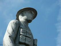 Memorial depicting world war 1 soldier. Stone sculpture to world war 1 dead depicting british soldier in uniform with rifle and wearing steel hat against blue Royalty Free Stock Images