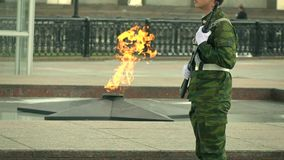 Memorial fire and armed guard in camouflage uniform. Super slow motion long shot. Eternal flame memorial and armed guard. Super slow motion video stock video footage