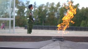 Memorial fire and armed guard wearing camouflage. Super slow motion long shot. Eternal flame memorial and armed guard. Super slow motion video stock video footage