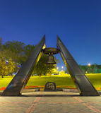Memorial monument with bell in park near stadium in Donetsk. Memorial monument for Defenders of Donbass, big bell, dark granite stone with text in center. Park stock photography