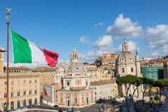 Memorial monument the Vittoriano or Altar of the Fatherland, in. Venezia square, with waving italian flag. Italian and Rome patriotic symbols, located on the Stock Photography