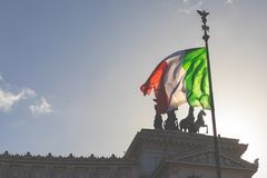 Memorial monument the Vittoriano or Altar of the Fatherland, in. Venezia square, with waving italian flag. Italian and Rome patriotic symbols, located on the Royalty Free Stock Photos