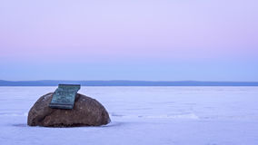 Memorial plaque on boulder on lake shore in winter Royalty Free Stock Photo