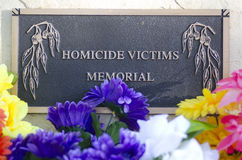 Memorial stone for homicide victims in cemetery. A memorial stone for homicide victims in a cemetery, with colourful flowers in the foreground stock image