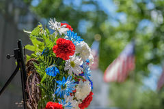 Memorial wreath laid in front of veterans memorial in park on sunny Memorial Day. Closeup macro of red white and blue flowers on wreath with soft blurred us royalty free stock photos